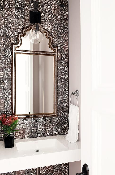 Mediterranean powder room features an accent wall clad in gray mosaic tiles, Cle Tile Origins Asal Tiles, lined with a Moroccan style mirror illuminated by a glass sconce over a white quartz floating sink vanity and a wall-mount faucet.