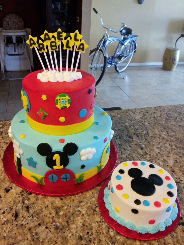 """Mickey Mouse Clubhouse cake - 7"""" and 11"""" rounds all frosted in Pastry Pride. Red tier was airbrused to achieve that shade of red. All decorations are gumpaste glued on with a little melted chocolate. 6"""" matching smash cake for baby!"""