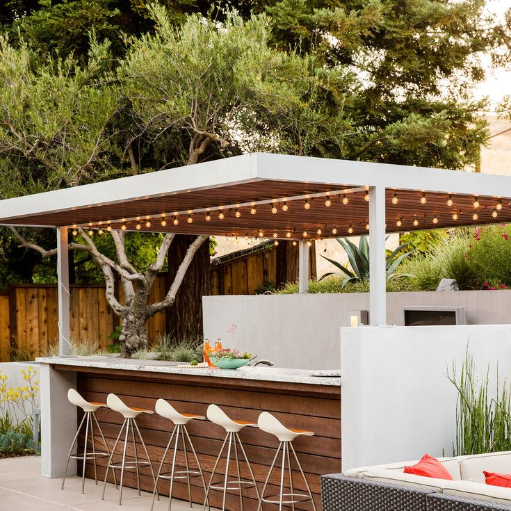 "Outdoor bar: Elaine Barden envisioned her backyard retreat as ""Palm Springs meets W Hotel style."" Her designers chose a custom fabricated aluminum arbor above an outdoor bar. The team built it on-site and painted it silver to match the wall sconces. Redwood slats cover the top."