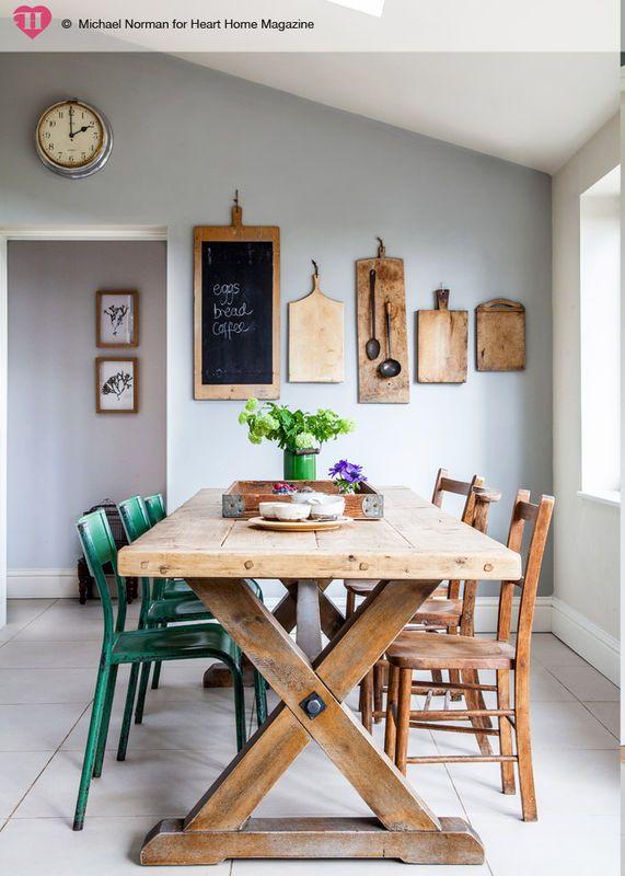Rustykalny stół na charakterystycznie skrzyżowanych nogach wniósł do tej jadalni sielankowy klimat. Przekornie zestawiono mebel z industrialnymi krzesłami z metalu. Pomalowane na zielono ożywiają stonowany skandynawski wystrój wnętrza.