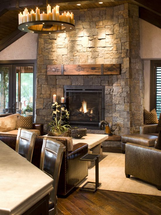 Love the contrast of colors, stone fireplace with wood mantle, candle chandelier, and leather sofas with white rug (a fur throw would be awesome!)