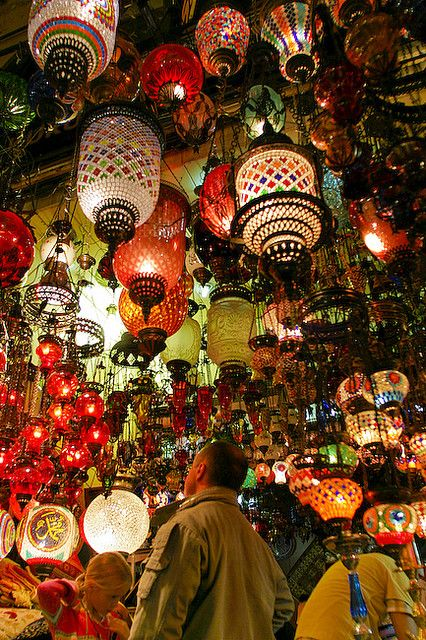 Photo of tourists from the inside of a small shop in the Grand Bazaar (Kapalıçarşı) selling colored lamps. A huge attraction for tourists, I personally very rarely saw merchants actually selling stuff and I kept wondering how the manage to make a living.