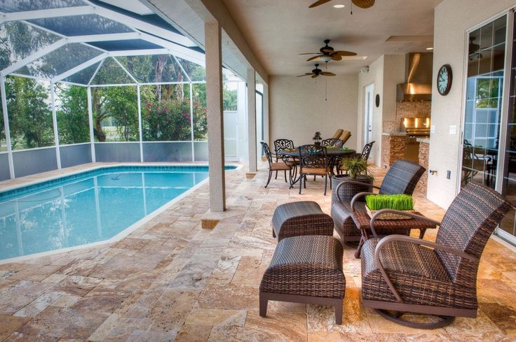 Tropical Patio with Indoor pool, Screen enclosure, Hospitality Rattan Grenada Wicker Swivel Rocking Chair, Outdoor kitchen