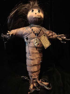 Voodoo Doll.  I have made a few and they are easier than you would think. Sticks tied in a cross, wrapped with moss and then fabric (glue or sew the end of the wrap) and decorate.