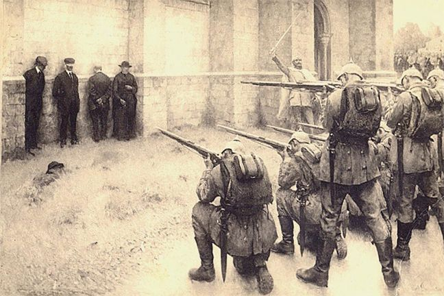 A line of soldiers take aim at a group of unarmed Belgian civilians, preparing to fire.