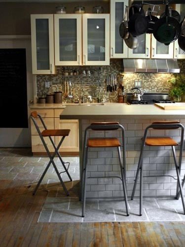 amazing kitchen...mixed old wood floors with tile, and folding stools at the island breakfast bar
