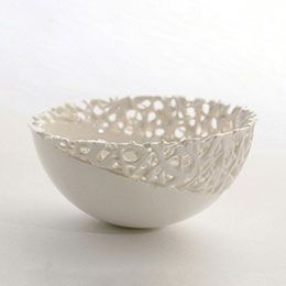 This website does NOT show how she does it, but this bowl is GORGEOUS. Perhaps she makes it by using slab clay inside a slump mold (or on a hump mold) and then using very thick slip trails to continue the design of the bowl? It would certainly be worth experiment to see whether it could be replicated.