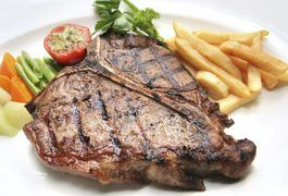 A T-bone steak contains a T-shaped bone in the center. It is made up of two different cuts, one on either side of the bone, the strip steak and the tenderloin. T-bone steak is tender and juicy with medium fat content that helps the meat retain flavor. Cook T-bone steak in a frying pan to crisp the exterior and lock moisture within.