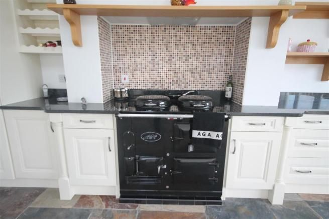 Neat black aga with onyx counters crisp white cabinets for Black onyx kitchen cabinets