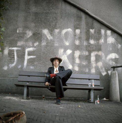 Henk Hilterman | Nederlands zanger Ramses Shaffy(1933-2009) zit op een bank ergens in de stad. Op de muur staat o.a het woord 'Molukkers' geklad. [Amsterdam], ca. 1965.