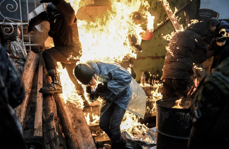 20.02.2014, UKRAINA, Kijów: Płonący przeciwnicy rządu podczas walk na barykadzie. AFP PHOTO/BULENT KILIC