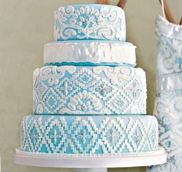 "Blue wedding cake. Lovin Sullivan Stylish Wedding Cakes    Bridal gowns – especially ornately adorned ones – provide an elegant source for lacy layers of icing. To echo the pastel underlay of this Reem Acara stunner, Sullivan covered a four tier cake in pale blue fondant. White royal icing and fondant mimic the embroidery, while silver dragees replicate the beads."" In Style Weddings"