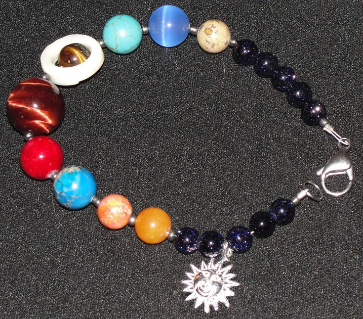 After finally seeing the true colors of Pluto, I have created a semi precious stone bracelet to symbolize all the known planets in our solar system.  The sun charms are sterling silver with the clasps being stainless steel.  The stones that make up the planets are: Mercury- orange quartzite V...