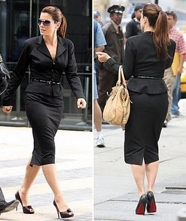 Sandra Bullock is wearing cinched-waist black suit that is paired with black Christian Louboutin peep-toed pumps and Prada bag