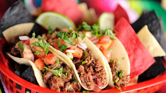 Tacos de barbacoa in corn tortillas topped with diced tomatoes and onions, and garnished with cilantro