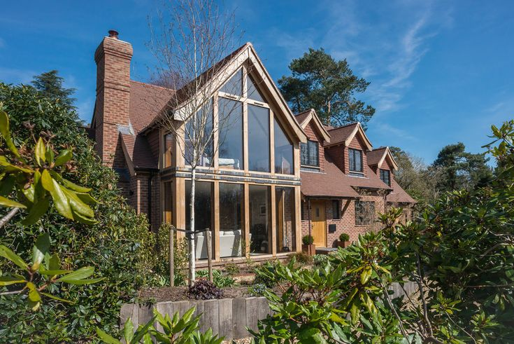 New Build Family Home, Storrington  http://www.jolliffdevelopments.com/past-work-gallery/rjjlrgh2ez56bjt36jymzpattgap3n South facing view of full height glazed gable end with Glulam timber frame, surrounded by mature landscaping.