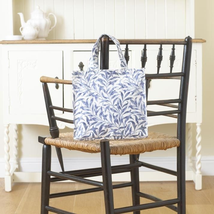 William Morris Willow Bough Blue Pvc /Oilcloth Small Floral Tote Bag. This Licenced William Morris Willow Bough Blue Design was first designed in 1887. It was first produced as a wallpaper design which William's daughter, May Morris used to decorate her bedroom before being adapted for fabric in 1895 when it was block printed in Merton Abbey.
