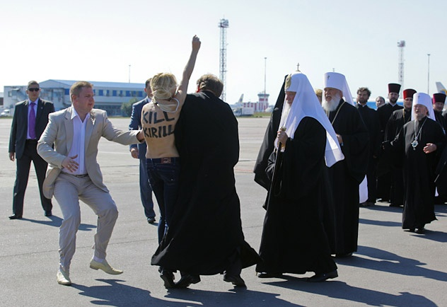 An activist from Ukrainian women\'s rights group FEMEN performs an act of protest against the Russian Orthodox Patriarch Kirill upon his arrival at the Kiev airport on July 26, 2012