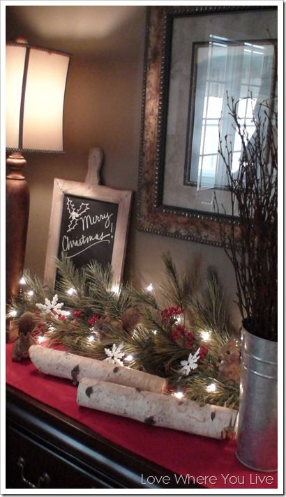 Lighted garland, a bucket of branches, birch logs and a few small woodland creatures for a simple nature-inspired holiday buffet