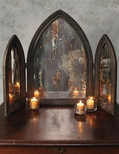 A gothic trifold mirror of mottled mercury glass conjures visions of gargoyles and towering medieval cathedrals.