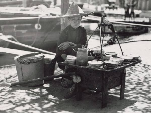 A Chinese woman selling hawker food on the banks of the Singapore River circa 1938 - 1939. Source: National Museum of Singapore
