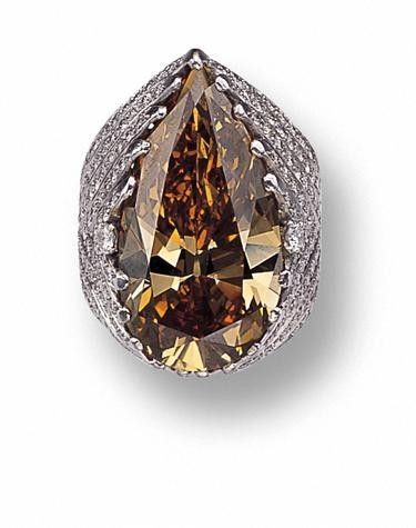 A pear-shaped Fancy Dark Yellow-Brown diamond weighing approximately 27.25 carats, within an openwork platinum mounting accented with 186 by shawna
