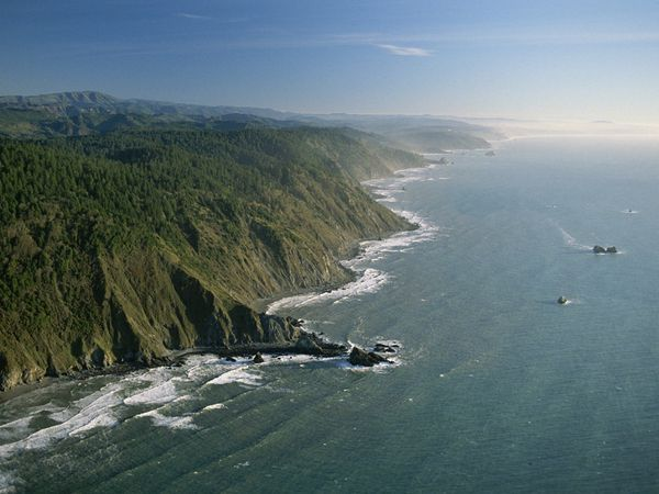 An aerial view of the Pacific shoreline shows the majesty of the cliffs near Crescent City, which is also home to the famous redwoods of northern California.