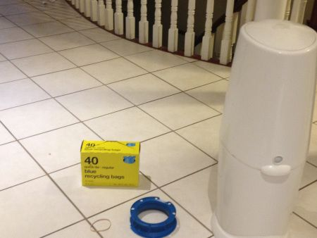 Use blue recycling bags and elastic band with empty diaper genie refill and save money!
