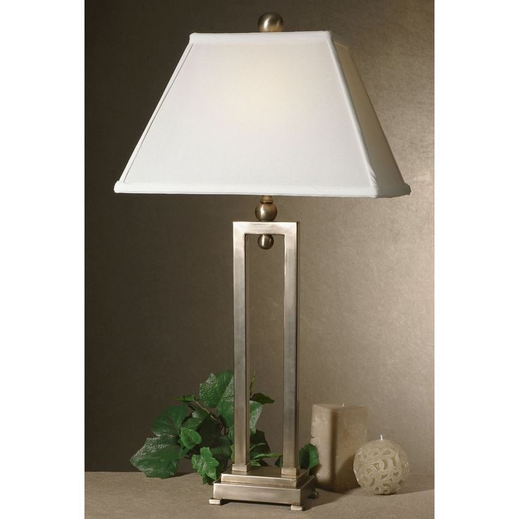 This contemporary Conrad table lamp has a silverplated body with a hand-applied antiqued stain. The rectangular bell shade is hand-sewn of ivory fabric.