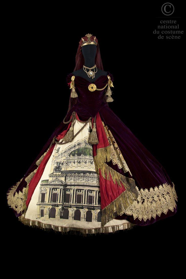 ¤ Melpomène.  Robe crinoline de style Second Empire. Corsage en velours rouge avec grand décolleté tombant sur les épaules. Garniture de passementeries de cordons or torsadés terminés par des pompons, maintenus par des cercles de métal or. Jupe en velours rouge bordée