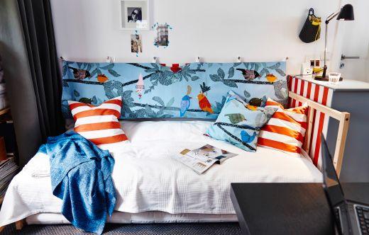 Blick auf FJELLSE Bettgestell in Kiefer mit weißer Bettwäsche und einem individuell gestalteten Kopfteil an der Wand.