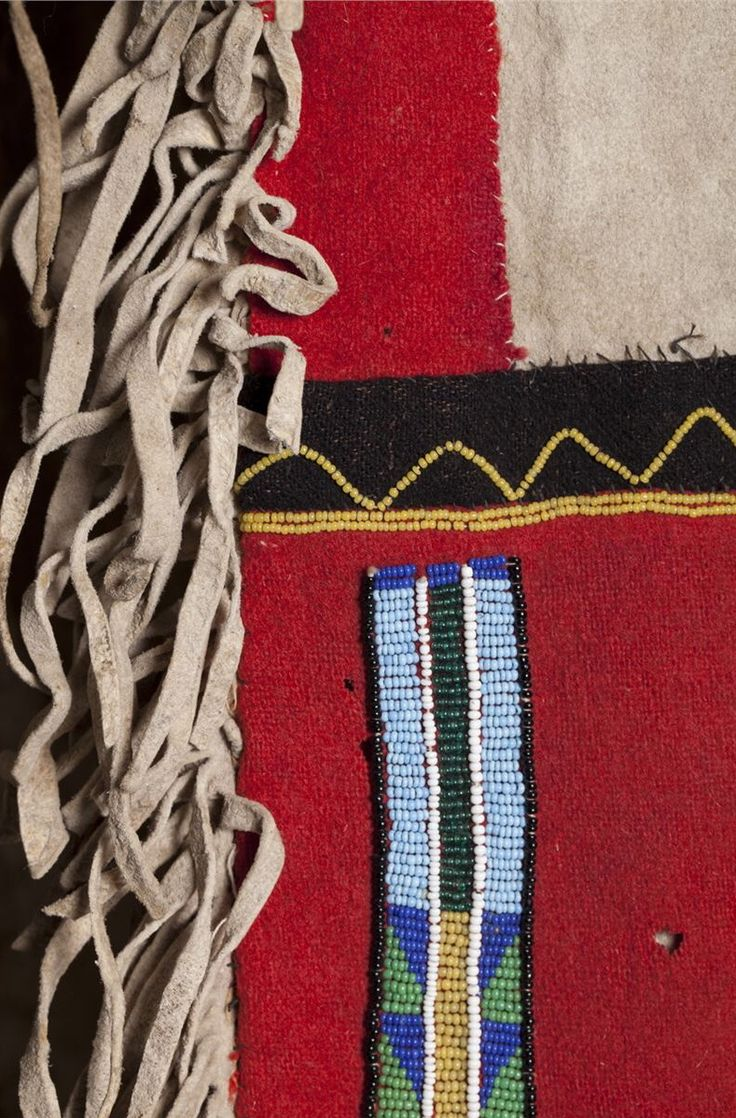 """Blackfoot Saddle Bags. ДА2. Pair of drape saddlebags or serapes with long 32"""" fringe, red trade cloth field with multicolored beading in geometric patterns. Black wool edging and accents. Fringed edge across the entire back. Green pigment. They hang at 54"""" making them 108 inches from the end of the fringe spread flat by 11"""" wide. The fringe is 32"""". Brian Lebel's High Noon Auction, Jun. 2015."""