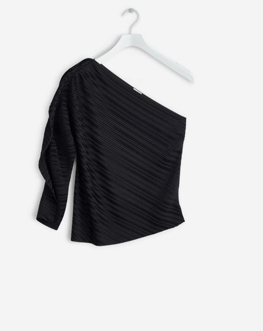 One shoulder top in luxurious plissé jersey. Sharply cut in one piece with laser-cut edges. Shaped arm with a graphic and soft frill.