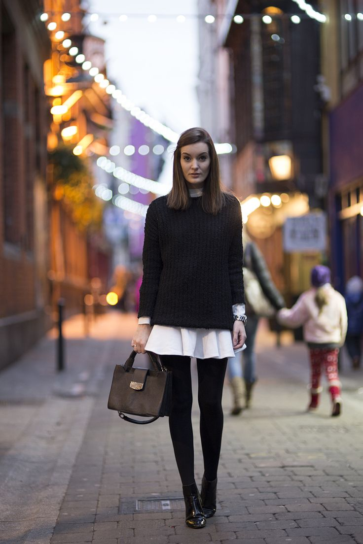 Chunky Black Knit Sweater, White Pleated Dress, Black Tights, Black Ankle Boots, Black Structured Bag, Sideswept Bangs, Blurred White Lights // city