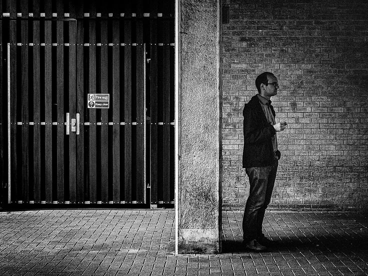 Smoking man...  Taken on a Saturday photowalk around Cardiff. Liked the way the bloke stood alone. Possibly waiting for someone, possibly on a much needed break. Loved the textures. It's quite a dark location at the back of St Davids Centre and pushed the ISO to add noise to the textures and shadows.  #Olympus m.zuiko 12-40 f2.8 pro lens @ ISO 1250 40mm f8 1/80sec
