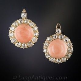Vibrant pink salmon colored coral buttons, by way of the late-nineteenth century Mediterranean sea, fill sparkling circles set with 2.00 carats of bright white old mine-cut diamonds in these cheerful, classic late-Victorian/Edwardian-era earrings, crafted in rosy-yellow gold with lever backs. They measure 5/8 diameter and drop down 3/4 inch.