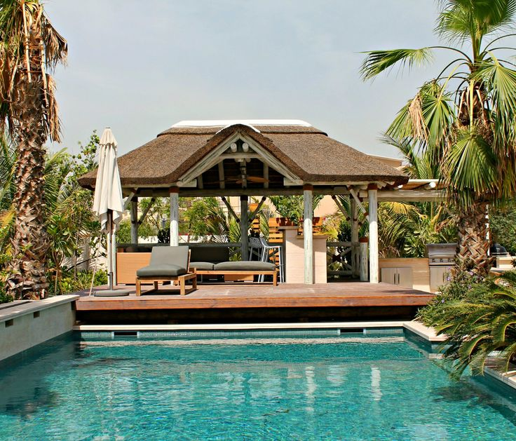 Outdoor living space with a whitewash thatched gazebo, pergola, outdoor kitchen with wooden deck overlooking the pool!!