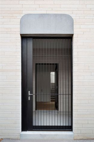 Thin black steel entry door designed by B.E Architecture for the Mountview Road Residence a modern reinterpretation of an old iron gate