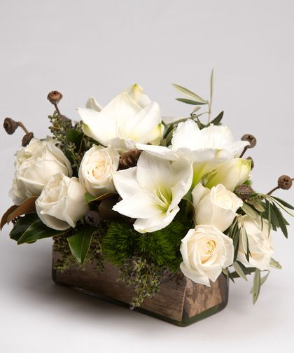 Winter Woodland Centerpiece A customer favorite, this stunning design of white roses, amaryllis, and hydrangea accented with seasonal favorites like magnolia and pinecones is gathered in a rectangular glass vase lined with birch bark.