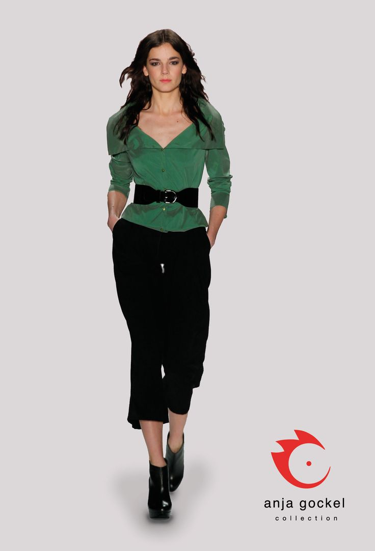 An exquisite outfit. A pair of luxurious silken black in combination with a taffeta blouse in shimmering green. The wide belt accentuates the waistline and adds a sexy feminine touch.