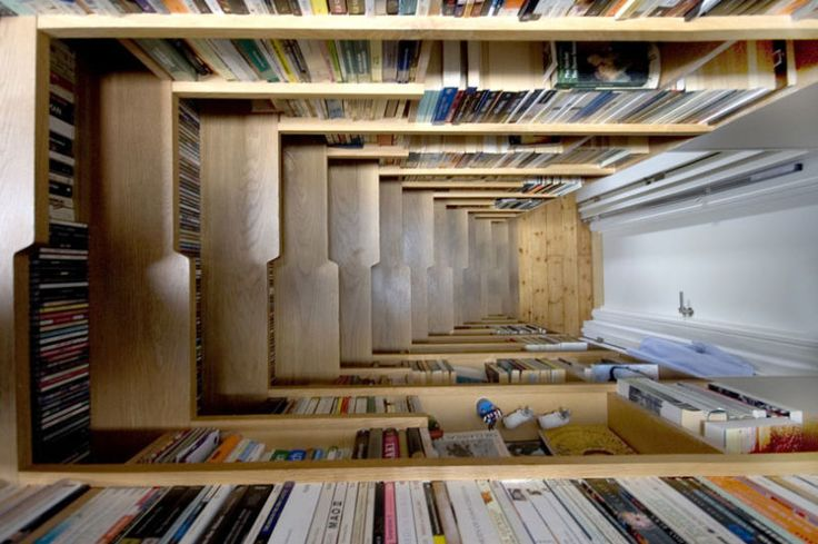 """Here's a great idea for anyone who loves books and doesn't have enough apartment space or a Kindle: a """"secret staircase"""" made of English oak, lined with books left, right and center, leading to a loft bedroom in a Victorian 1898 apartments block."""