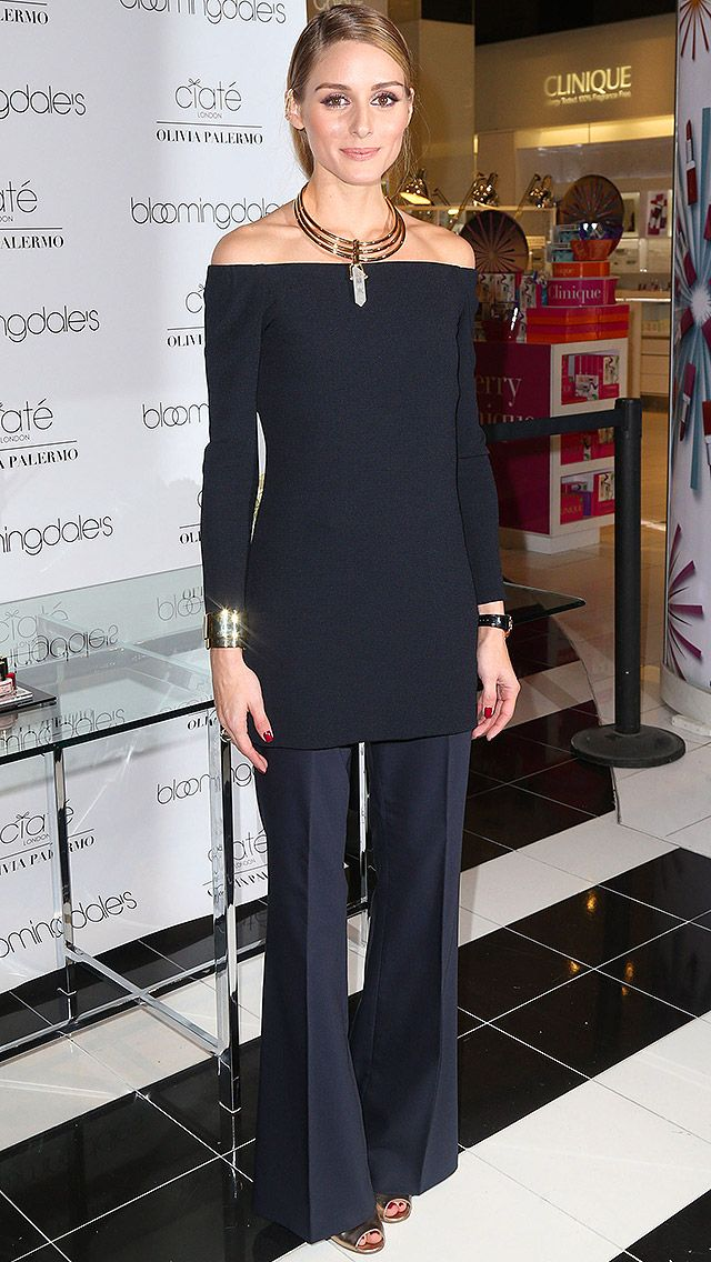 OLIVIA PALERMO in an off-the-shoulder black sweater, wide-leg trousers and gold jewelry