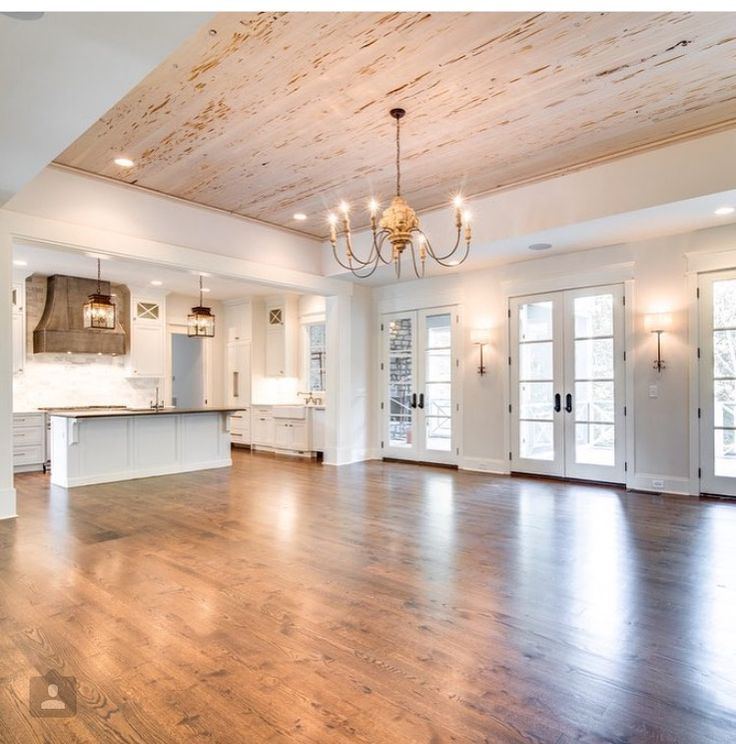 Open concept living area with lots of natural light, hardwood floors, rustic wood ceiling, white trim & cabinets