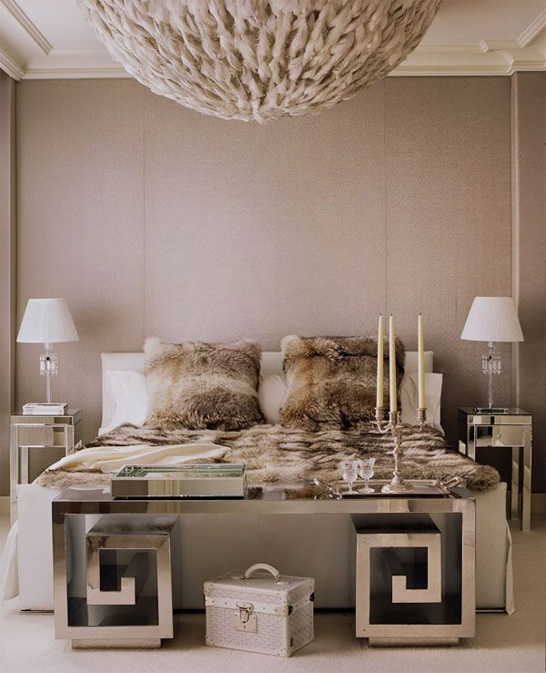 Exceedingly glamorous bedroom in shades of taupe, beige, cream and gray. Fur pillows, an oversized chandelier and that amazing mirrored greek key bench add luxury and wow factor!