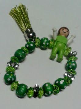 Bracelet vert en perles et breloques. Soldé à 50%. Élastiqué, convient autant à un enfant ou'à un adulte. Breloques: bébé Playmobil. miniature et pompon.  Détournement - Artisanat miniature - Fait main - Prix soldé: 6€   Avec ses perles translucides, ses perles à pois ainsi que ses perles argentées, complété par ses pendentifs, miniature et pampille, le tout dans un camaïeu de vert, ce bracelet donne au poignet un petit air mutin et enjoué. Coloré, unique et idéal car il peut se porter avec…