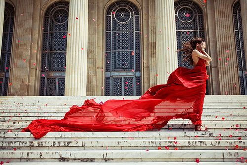 this is a beautiful dress, billowing in the wind, and the color, and the rose petals blowing in her face! It is a beautiful photograph
