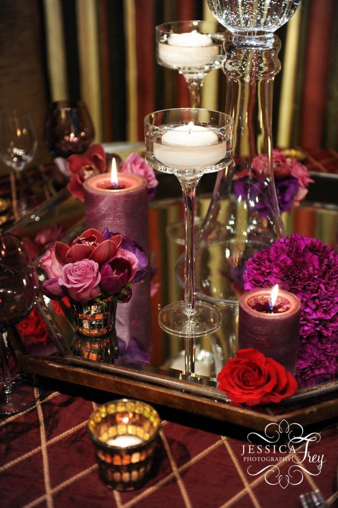 Purple carnation pomander balls, lavender roses, purple lisianthus, purple tulips, and red cymbidium orchids. With candles and red roses decorating the mirror. #naakitifloral