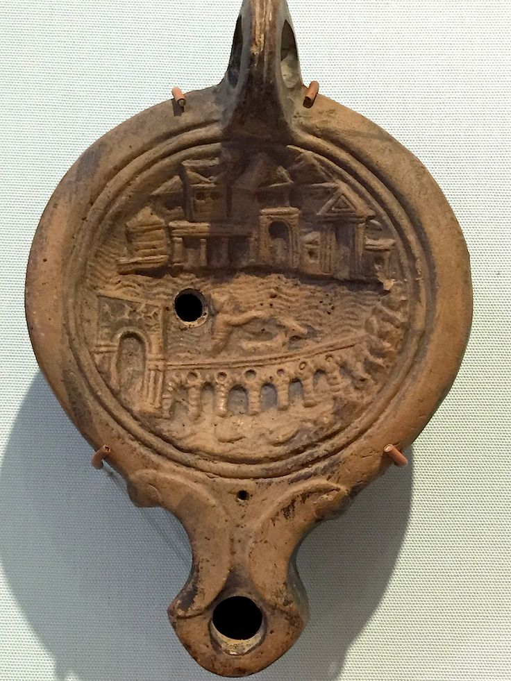 Oil lamp showing a harbour, perhaps Alexandria. This one is from the Museum of Archaeology and Anthropology at Cambridge. Photo by Caroline Lawrence, author of The Roman Mysteries. 2014.