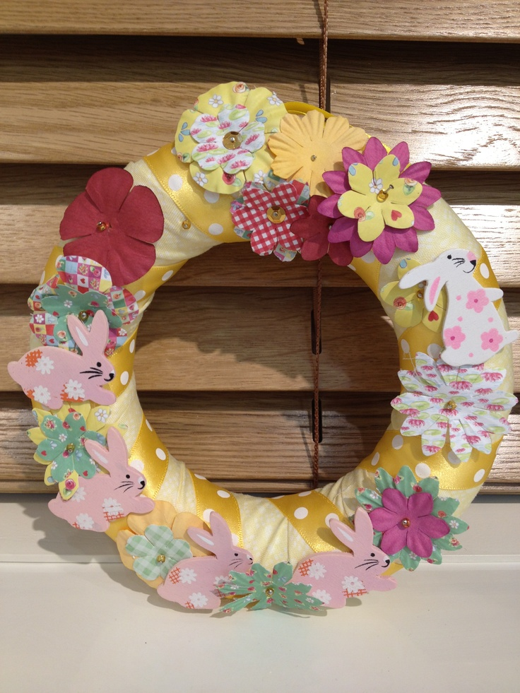 Polystyrene wreath wrapped with fabric and ribbon, with pinned paper flowers