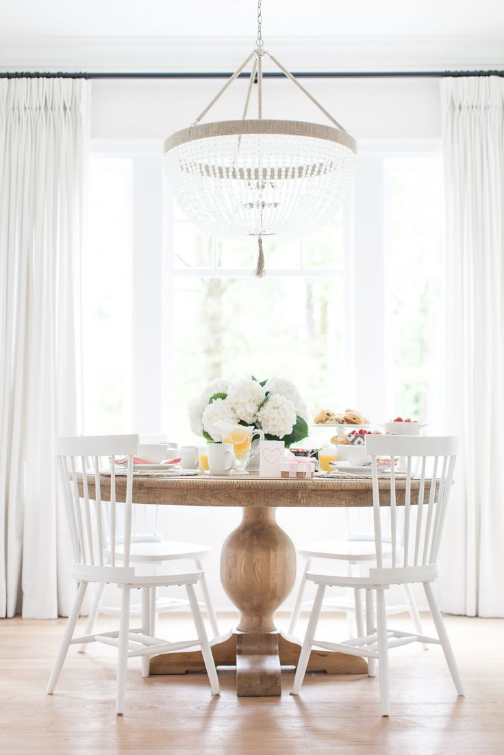 An airy, bright, dining nook complete with a pedestal table and beaded tassel chandelier.
